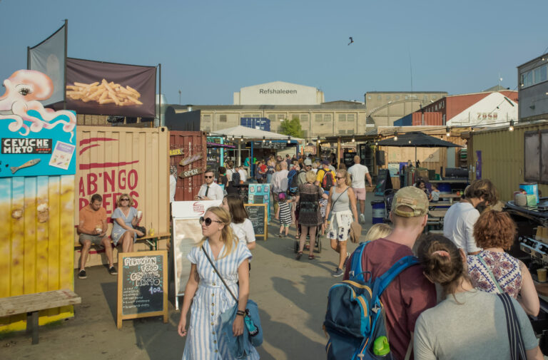 An outdoor market bustling with people on a nice summer day