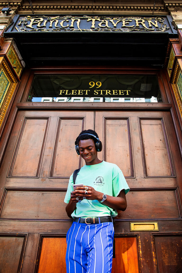 A young man is standing in front of a door. He is wearing headphones and looking at his phone, smiling.