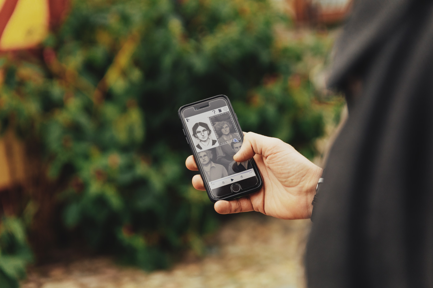 A man is holding a smartphone. On the screen is a portrait of a woman