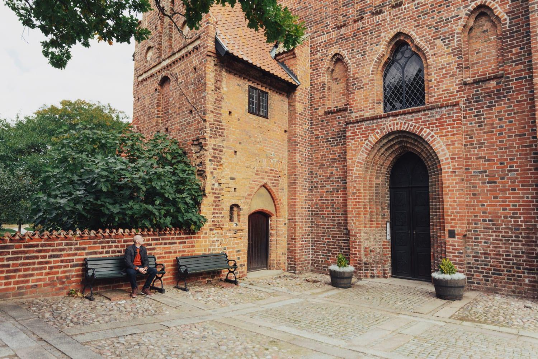 A man is sitting on a bench next to Ystad klosterkyrka