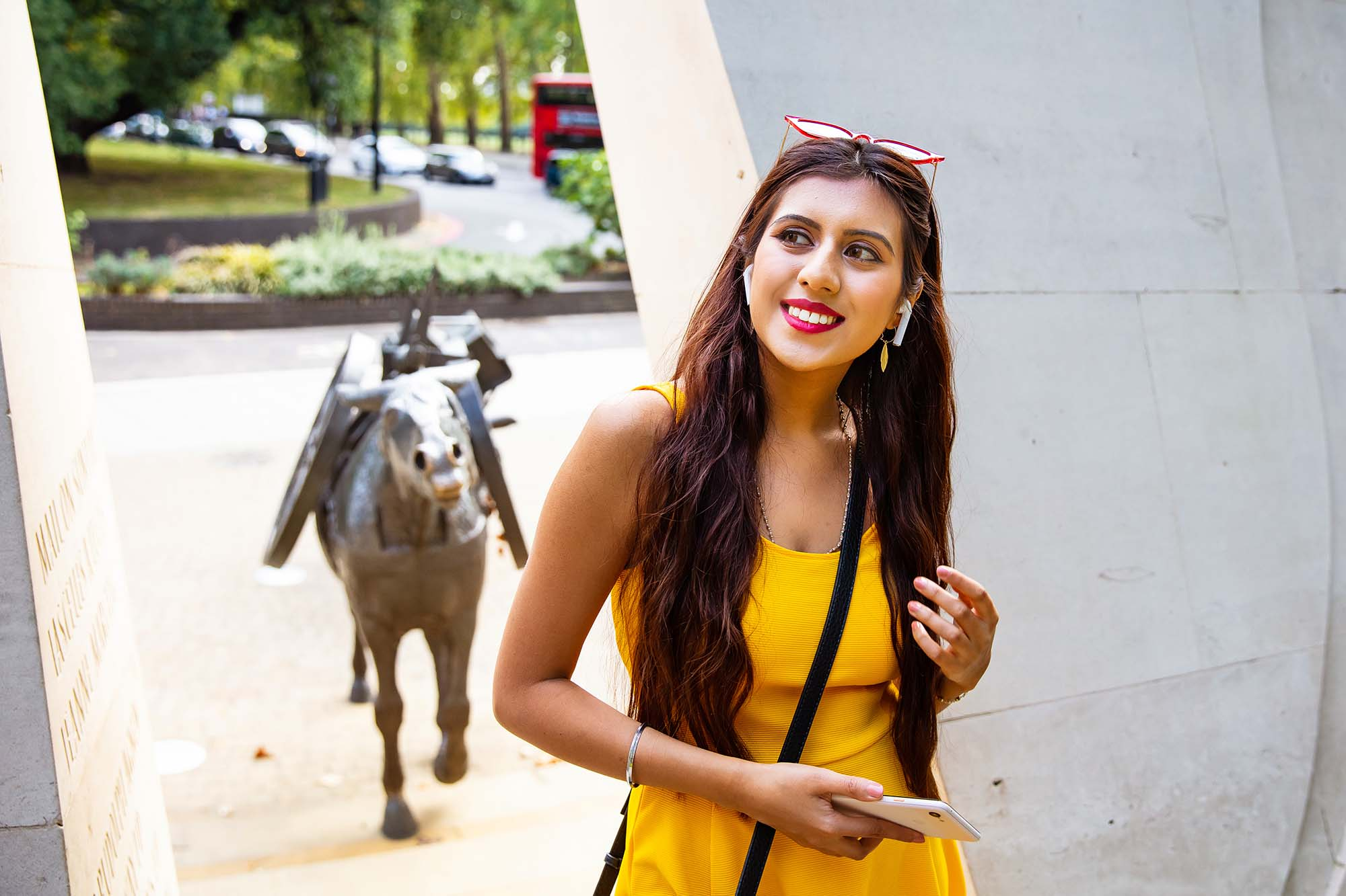 A young woman in a yellow dress is exploring the animals in war memorial in London