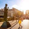 A young woman in a yellow dress is standing in front of the Sherlock Holmes statue on Baker Street