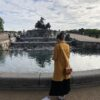 A young woman wearing a yellow coat is standing in front of the Gefion fountain in Copenhagen