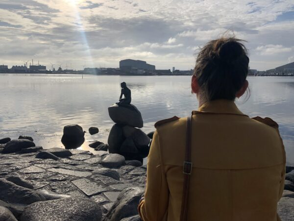 A woman in a yellow coat is looking at The Little Mermaid statue