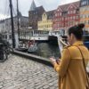 A woman in a yellow coat is walking through Nyhavn