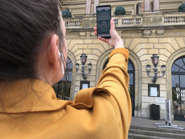 A woman in a yelow coat is atnding in front of the Danish Royal theatre. She is holding up her smartphone