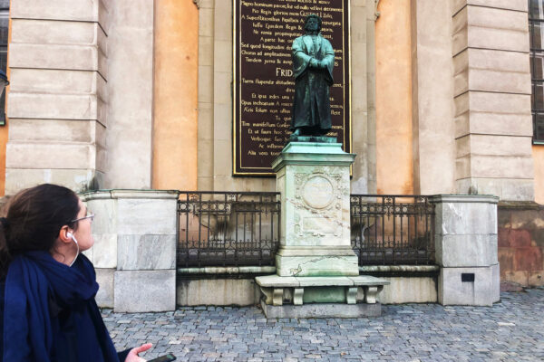 A woman in a blue coat is looking up at a bronze statue of a man