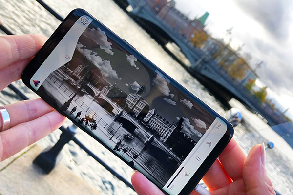 A woman is holding a smartphone, an old black and white photo is visible on the screen
