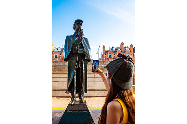 A young woman in a deerstalker hat is taking a picture of a Sherlock Holmes statue
