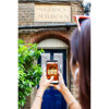 A woman is holding up her smartphone against a brick facade with a signs that says Sarsden building