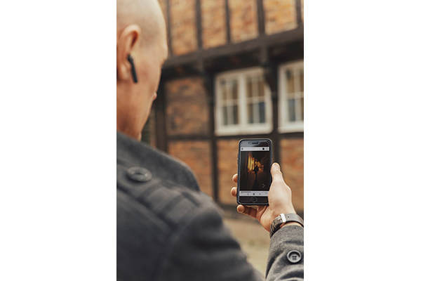 A man standing in front of a half timbred house is holding up his smartphone